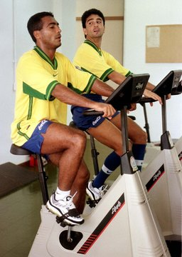 Brazilian strikers Romario (L) and Bebeto work out on lifecycles at the team training facility in Te..