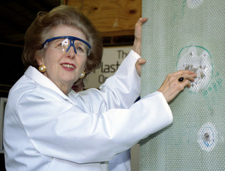 Baroness Margaret Thatcher examines  a sheet of bullet-proof material  during a visit to a factory p..