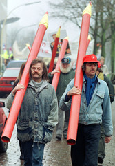 Protesters with oversized red pencils, a German symbol for public sector spending cuts, walk to a de..