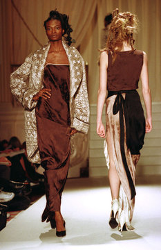 A model wears a brown silk evening dress and a patterned gold coat as she passes another model durin..