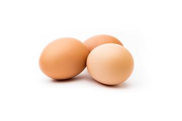 Tres huevos morenos con fondo blanco