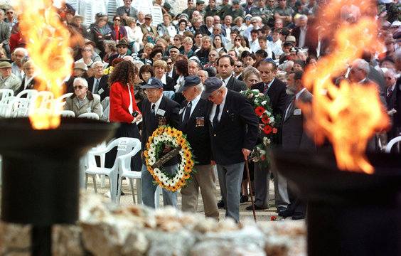 Holocaust survivors carry a wreath of flowers May 5 in the Yad Vashem Holocaust Memorial as they par..