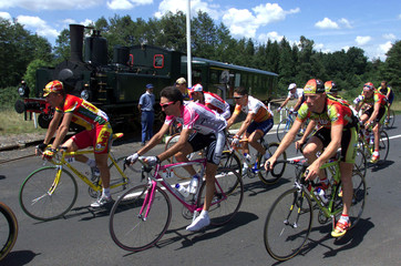 The riders of the Tour de France cycling race pass a steam train during the 12th stage  from St Galm..
