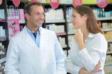 woman talking to pharmacist in drugstore