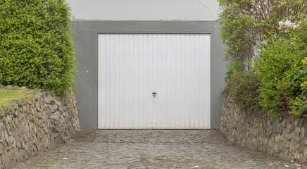 Weißes Garagentor mit grauer Fassade