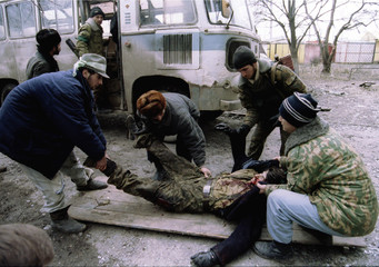 Chechen fighters lift the body of a comrade in Minutka square January 14. Six Chechens were killed a..