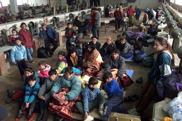 ETHNIC ALBANIANS SIT IN A REFUGEE CAMP.