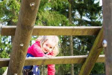 Blondes Kind klettert und hat Spaß