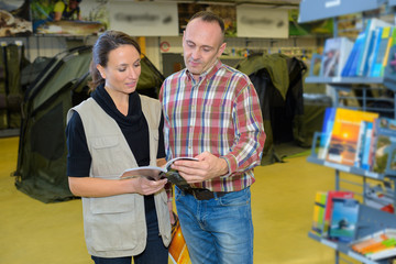 sales assistant showing customer tents catalog in outdoors store