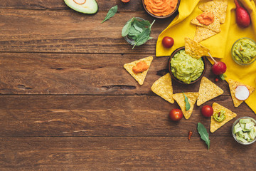 Fresh ingredients for homemade guacamole (avocado, tomato, salt) on wooden background. top view. Healthy food background with space for text.