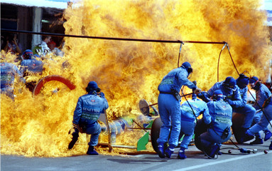 The Benetton Ford of Netherland's Jos Verstappen is on fire as the crew tries to escape during refue..