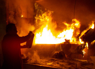 A Greek shop owner tries to extinguish a fire in his shop set alight by anti-U.S. protestors in cent..
