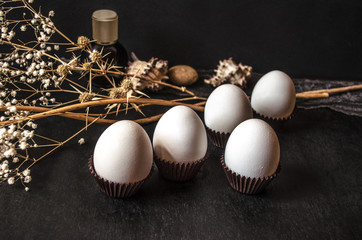 White eggs in corrugated paper capsule with dry twigs on a black background
