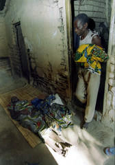 The husband of a woman who died of the Ebola virus brings out her clothing May 19 to be buried along..