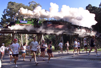 A STEAM TRAIN RACES RUNNERS DURING A FOOT RACE NEAR MELBOURNE.