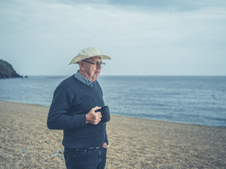 Senior man on beach with cup of drink
