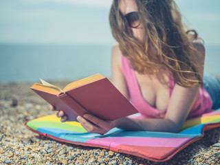 Woman reading book on beach in the summer