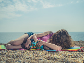 Woman breastfeeding baby on the beach
