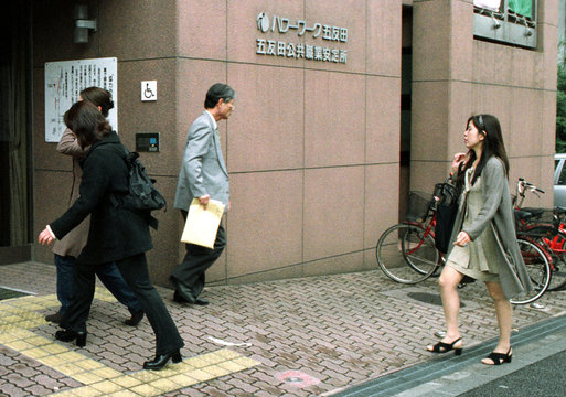 Young Japanese women enter an unemployment office as a middle-aged man leaves  in Tokyo April 28. Ja..