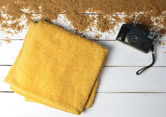 A beach towel and  vintage camera on a white wooden surface. The concept of relaxing at sea. Summer beach season is open! Top view.
