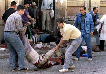 PEOPLE HELP WOUNDED OUTSIDE OF THE INDOOR MARKET IN SARAJEVO.