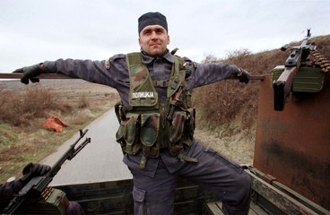 A Serbian special police forces officer in battle gear, atop a make shift armoured truck, relaxes Fe..