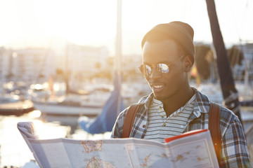 Fashionable young dark-skinned man surrounded by yachts and ships using paper guide while having walk in foreign city, traveling around the world during summer vacations, feeling happy and free