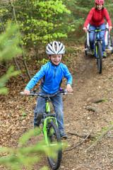 kleiner Mountainbiker im Wald unterwegs