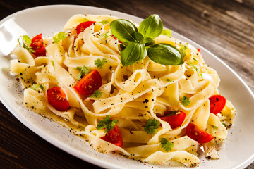 Pasta with tomatoes on wooden table