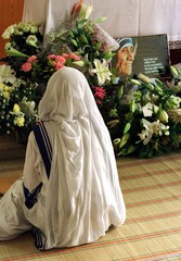 A nun sits beside a portrait of Mother Teresa September 8 at the Missionaries of Charity in Hong Kon..