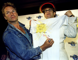 Pop star Sting signs his name alongside a cartoon of himself on a T-shirt held by Elton John July 26..