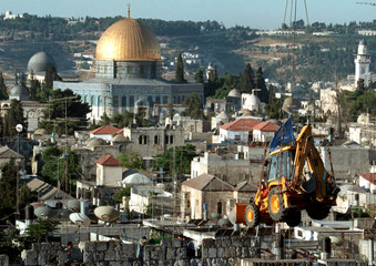 A small bulldozer is lifter over the walls of the Old City early June 8 in order to begin digging at..