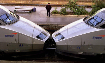 An unidentified walker passes by high speed trains on an empty platform at Nice's railway station De..