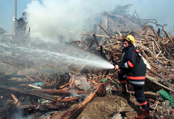 Firemen extinguish a fire after a NATO missile hit the centre of Kosovo's capital of Pristina early ..