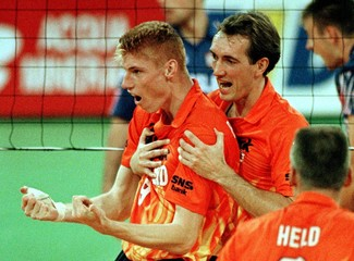 Dutch volleyball player Peter Blange (R) holds his team mate Bas van der Goor after scoring a point ..