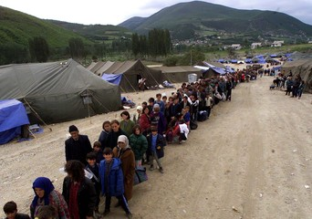 Ethnic Albanian refugees queue to board buses at the holding camp at the border between Yugoslavia a..
