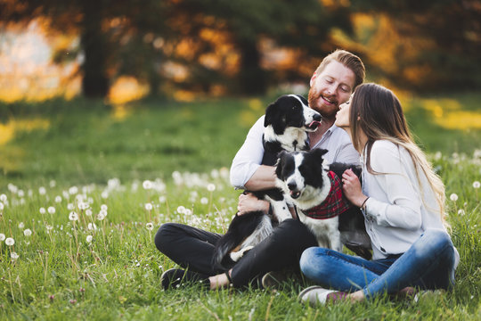 Beautiful couple cuddling and walking dogs outdoors