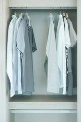 Men's cloths hanging in white wardrobe