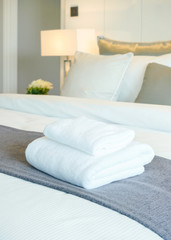 White towels on bed in modern bedroom interior