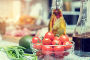 Raw fresh cherry tomatoes in glass bowl in a modern kitchen. Shallow depth of field. Toned