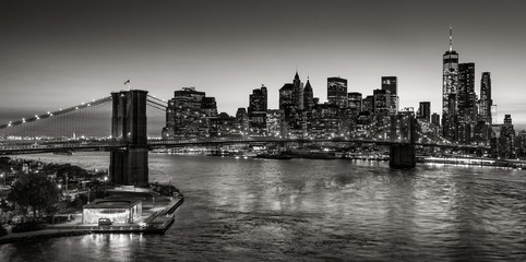 Wall Mural - Black & White elevated view of the Brooklyn Bridge and Lower Manhattan skyscrapers at dusk. Skyline of the Financial District with East River. New York City