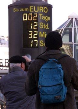 TWO MEN TAKE PHOTOGRAPHS OF EURO CLOCK.