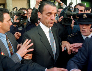 Disgraced former Banesto bank chairman Mario Conde is surrounded by bodyguards, pressmen and policem..