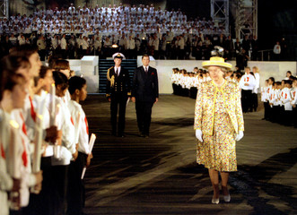 """Britain's Queen Elizabeth II walks past a children's candlelight chorus during the finale of the """"Be.."""