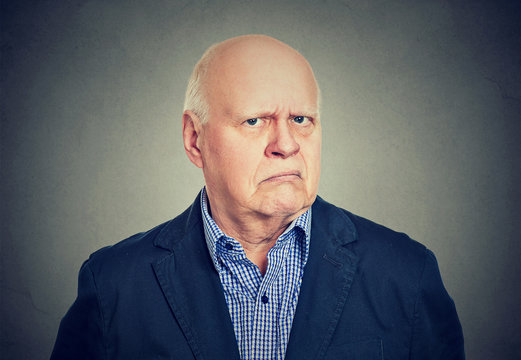 Angry, grumpy senior business man, isolated on gray background
