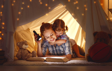mother and child daughter with a book and a flashlight before going to bed.
