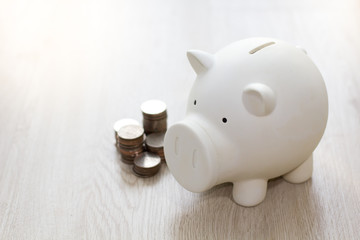 White piggy saving money with coin on wooden floor.