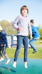 Glückliches Mädchen springt auf dem Trampolin