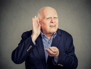 Senior man, hard of hearing, placing hand on ear asking someone to speak up