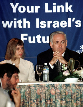 """Prime Minister Benjamin Netanyahu sits with his wife Sara on a podium under a banner reading """"Your L.."""